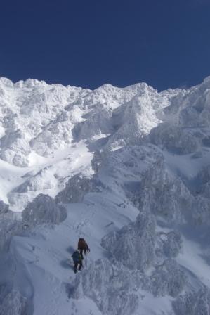 ④上部岩壁への雪稜を行く前パーティ